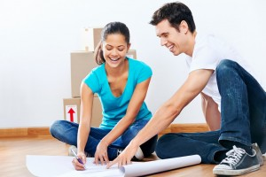 couple moving into new home looking at floor plans together